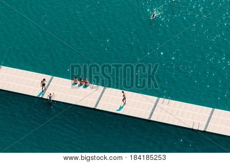 Unrecognizable people enjoying hot summer afternoon on lake Bled aerial view of leisure and recreational activity for holiday vacation in Slovenia