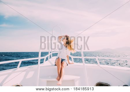 Cheerful Young Woman Leaning At The Handrail And Smiling At Camera While Standing On The Ship's Bow