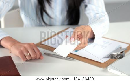 .Businesswoman holding blank visit card , sitting on the desk.