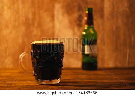 Dark beer in british dimpled glass pint mug on bar table