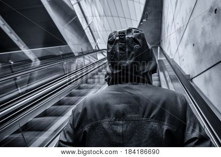 Unrecognizable hooded person on moving escalator in modern urban interior surroundingmonochromatic image with selective focus