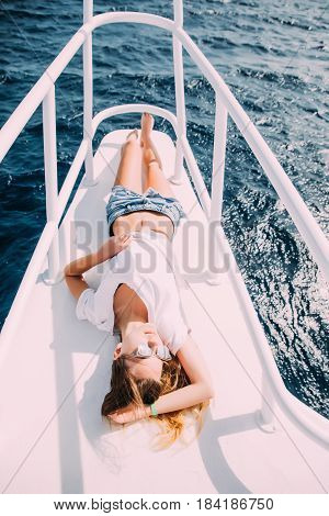 Carefree Time On Yacht. Beautiful Young Woman In Eyewear And Smiling While Lying On The Deck Of Yach