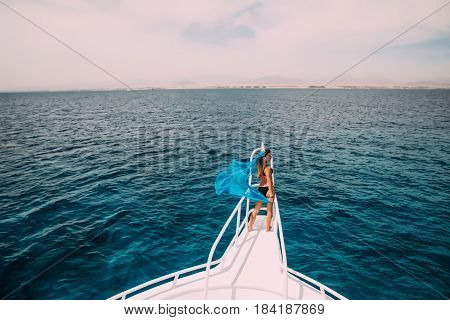 Beautiful Woman On Yacht Nose With Blue Scarf Wave On Wind. Summer Time Vocation On Yacht.
