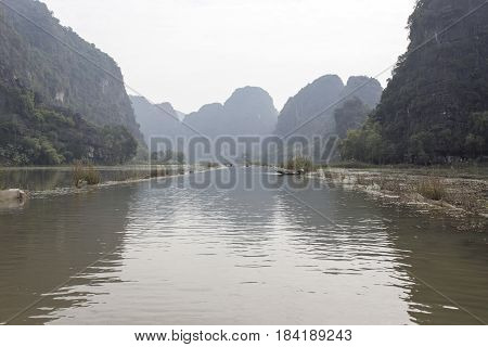 Early morning and fog at Tam Coc - Bich Dong tourist destination near Ninh Binh Vietnam