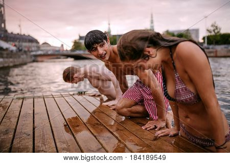Side view of young people on the edge of the pier at lake. Woman with friends coming out of the lake after a swim.