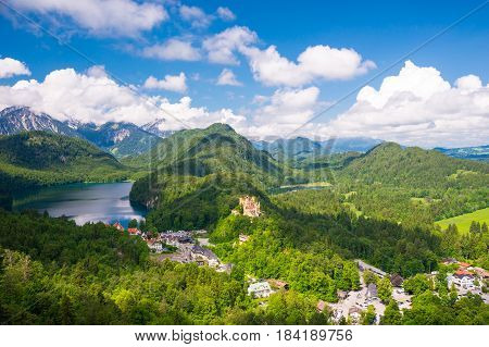 Castle Hohenschwangau, eternal forest with blue mountains and lakes of Bavaria, Germany.