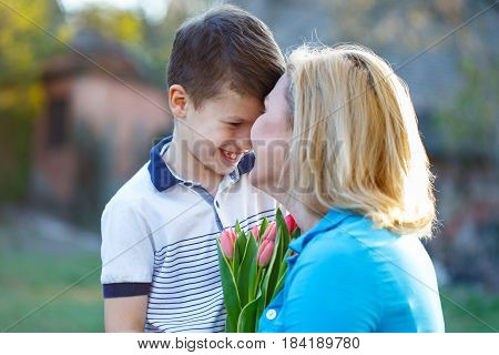 Happy mother get tulips from son at mothers day surprise