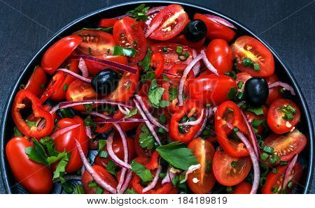 Fresh salad of tomato, onion, pepper, greens and oil on a black plate, black background. Red on black