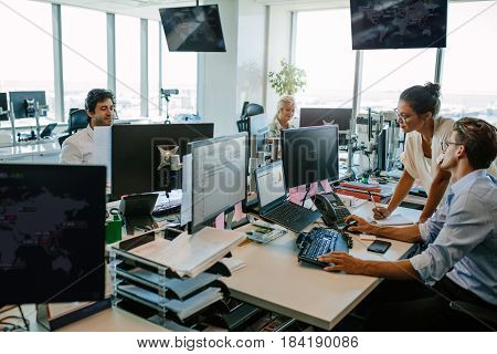 Business people working in modern office. Team working at desks in busy office.