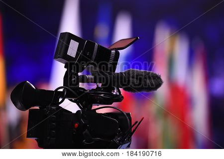 Modern digital television or video camera camcorder recorder in studio on blurred colorful background. Broadcasting media entertainment