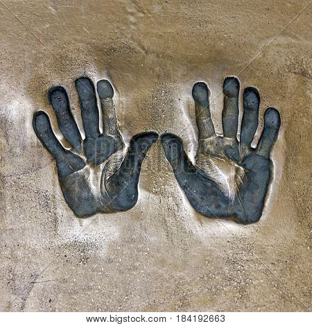 Print of hands. Both hands print on cement mortar wall with shadow relief