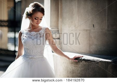 The charming bride stands near  the building