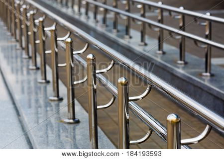 Chromium metal fence with handrail. Chromium metal railings. Shallow depth of field. Selective focus.