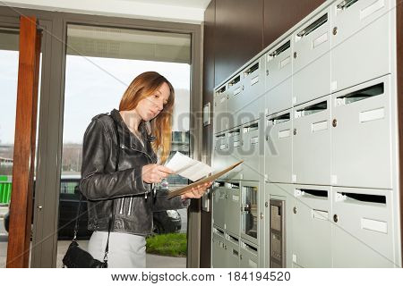 Portrait of pretty woman checking junk mail standing at the hall