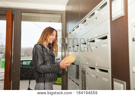 Happy young woman holding parcel in her hands standing next to mailboxes