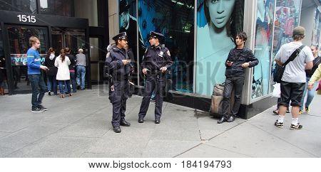 Two American Policewomen Patrolling City Street In New York, Usa
