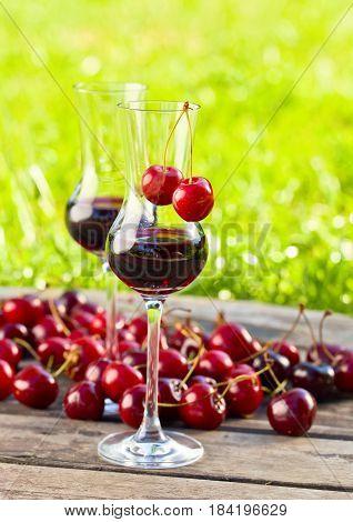Glass of Cherry liquor and juicy ripe berries