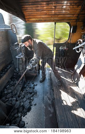 The stocker feeds the coal boiler while the steam locomotive runs at full speed in the countryside