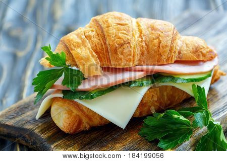 Croissant With Ham, Cheese, Cucumber And Parsley.