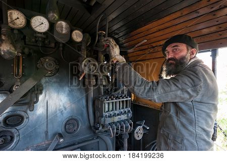 The train driver near the steam locomotive boiler keeps an eye on the vapour pressure