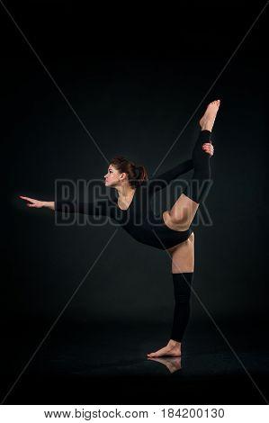 Sporty gymnastics woman stretching on One leg on black background
