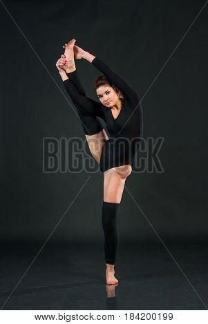 Sporty attractive woman stretching in One legged Wheel exercise Wearing sportswear isolated black studio background