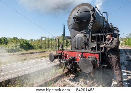 Steam locomotive stops on the tracks snorting smoke and hot steam