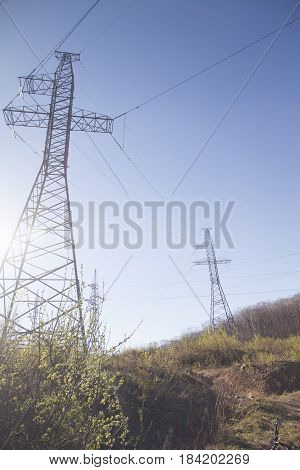 Power line support in the bright sunny day against the background of the blue sky