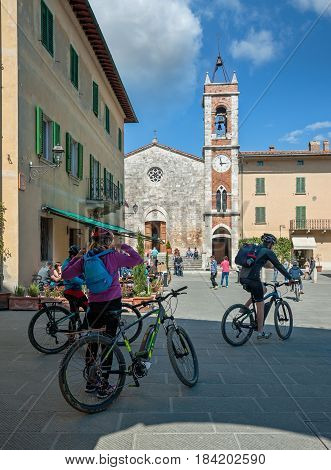 San Quirico d'Orcia, Tuscany, Italy - April  23, 2017: Cyclists with mountain bikes in front of the church of San Francesco, in the center of the village.