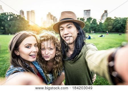 Multi-ethnic group of friends in Central Park Manhattan - Young cheerful people bonding outdoors