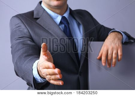 Man wearing a suit offering to shake hands .