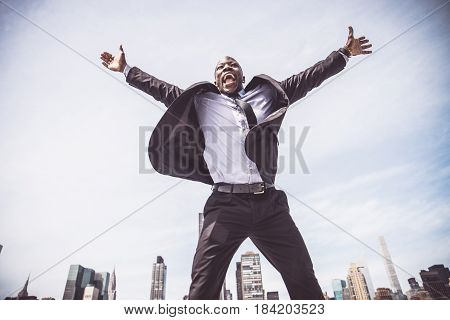 Confident happy businessman exulting and jumping outdoors