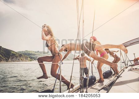 Multiethnic group of friends sailing on a boat - Summer holidays young adults having fun