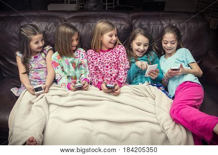 Group of little girls playing with their electronic mobile devices and smart phones with sitting on the couch together at a slumber party