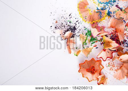 Wooden colorful pencil sharpening shavings on white as abstract background. Art and education