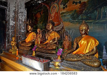 Buddha in the golden covering in the temple where pilgrims and tourists come to get knowledge and pronounce the mantra