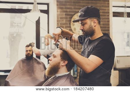 Man getting haircut by hairstylist at barbershop. Stylish barber and client