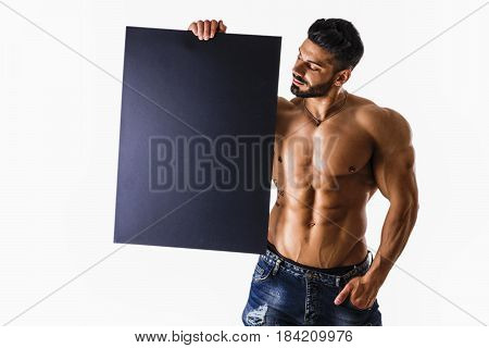Naked young male bodybuilder holding blank black sign, isolated on white background, large copyspace