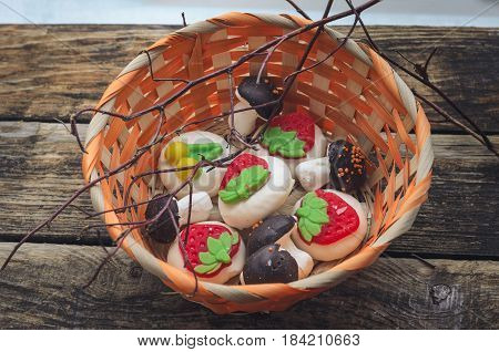 Wicker basket with sweet marshmallow nd branches of a tree