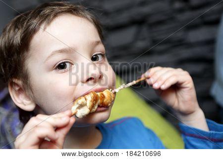Child eating chicken kebab in a restaurant