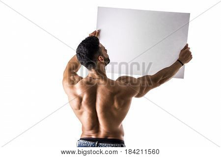 Naked young male bodybuilder holding blank white sign, isolated on white background, seen from the back, large copyspace