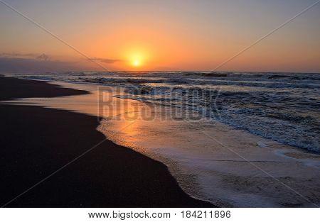 Preciosos reflejos sobre el agua de la orilla del mar de las tonalidades típicas del amanecer