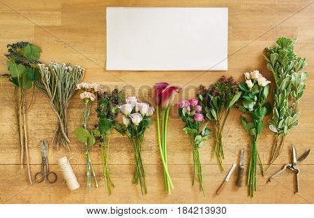 Empty white paper sheet with copy space and fresh flowers bouquets and blackberries on wood background, top view. Roses and coral callas