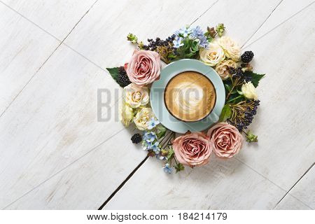 Cappuccino and flowers composition. Blue coffee cup with creamy foam, fresh and dried flowers circle at white wood background, top view, copy space