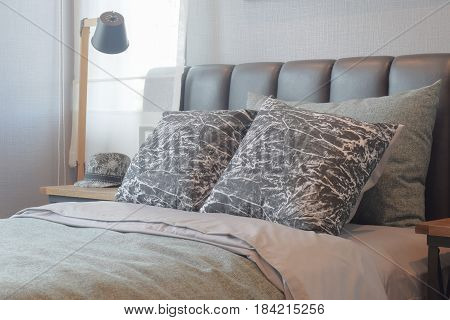 Black And White Pattern Pillows Setting On Bed With Black Leather Headboard