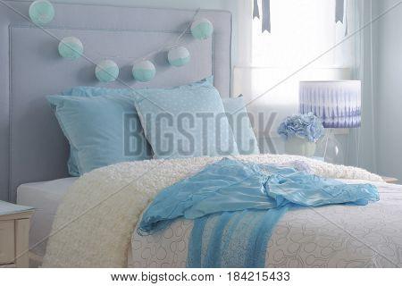 Light Blue Chiffon Dress On Beige Puffy Blanket In Light Blue Interior Bedroom