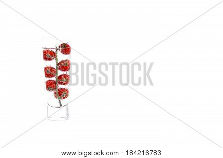 Cherry tomat in glass of mineral water, isolated on white background