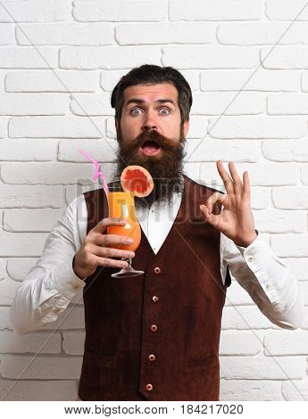 handsome bearded man with long beard and mustache has stylish hair on surprised face holding glass of alcoholic beverage in vintage suede leather waistcoat o white brick wall studio background