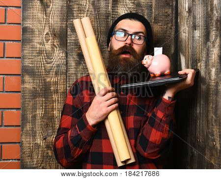 Bearded man long beard. Brutal caucasian surprised unshaven hipster holding craft paper rolls piggy bank on laptop in checkered shirt with hat and glasses on brown vintage wooden studio background