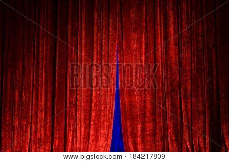 Red curtain in the dimly lit hall of the theater. In the interval between the parts of the curtain, the blue illumination of the scene is visible.